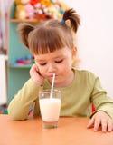 La bambina tenebrosa beve il latte immagine stock