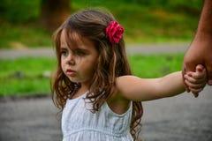 La bambina tiene dalla mano con un fiore in suoi capelli fotografia stock libera da diritti