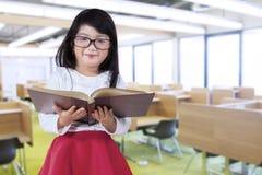 La bambina tiene il libro nella sala di lettura Fotografia Stock Libera da Diritti