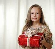 La bambina tiene una casella rossa con un regalo Immagini Stock Libere da Diritti