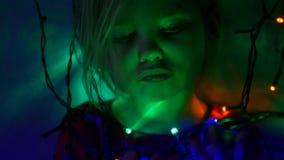 La bambina tocca la sfera variopinta vicino alle lampade leggere della ghirlanda nello scuro stock footage