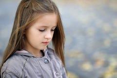 La bambina triste guarda da parte in autunno nel parco Immagini Stock