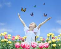 La bambina in tulipani con le mani aumenta e farfalla Fotografia Stock Libera da Diritti