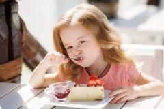 La bambina in un caffè di estate Immagini Stock