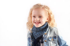 La bambina in un rivestimento blu del denim sta sorridendo Fotografie Stock Libere da Diritti