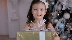 La bambina in un vestito bianco tiene un regalo del ` s del nuovo anno archivi video