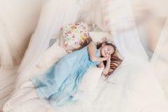 La bambina in un vestito blu sorride in un sogno Immagine Stock