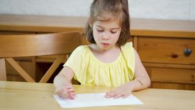 La bambina in un vestito giallo con una matita attinge la carta archivi video