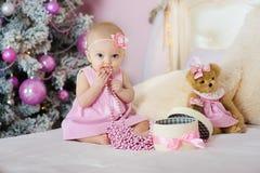 La bambina in un vestito rosa che si siede sul letto e tira dentro le sue perle della bocca per l'abete rosso Nuovo anno Fotografia Stock