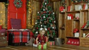 La bambina in un vestito rosso è giocata dai giocattoli su un fondo dell'albero di Natale video d archivio