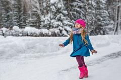 La bambina vestita in un cappotto blu e un cappello rosa e gli stivali, divertimento passa la foresta dell'inverno fotografia stock