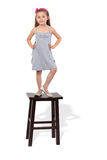 La bambina in vestito si leva in piedi sulle feci Immagine Stock