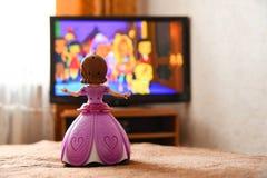 La bambola del giocattolo in un vestito rosa sta guardando un fumetto sulla TV fotografia stock
