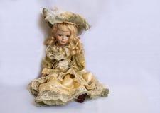 La bamboletta si siede su fondo bianco Fotografie Stock Libere da Diritti