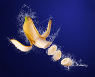 La banana affettata il colore giallo in acqua spruzza Fotografie Stock Libere da Diritti
