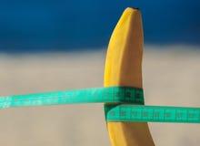 La banana con nastro adesivo di misurazione ha allungato sulla spiaggia Fotografie Stock Libere da Diritti