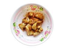 La banana conservata fruttifica sciroppo sul piatto bianco, plumeria fiorisce O Fotografie Stock