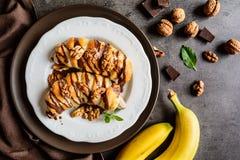 La banane cuite au four a enduit en pâte feuilletée, complétée du chocolat et des écrous Photos libres de droits