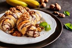 La banane cuite au four a enduit en pâte feuilletée, complétée du chocolat et des écrous Photographie stock libre de droits
