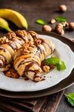 La banane cuite au four a enduit en pâte feuilletée, complétée du chocolat et des écrous photographie stock