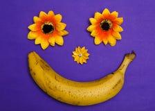 La banane et les fleurs font le sourire heureux sur le collage abstrait étendu parappartement violet de vue supérieure de bacgrou Images stock
