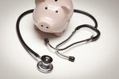 La Banca Piggy e stetoscopio con il fuoco selettivo Immagini Stock Libere da Diritti
