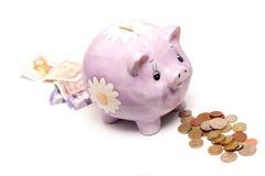 La Banca Piggy, monete nelle note. Fotografie Stock Libere da Diritti