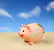 La Banca Piggy nella regolazione della spiaggia Immagini Stock