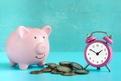 La Banca Piggy su una priorità bassa blu Vicino ad un mucchio delle monete e di una sveglia rosa Il simbolo è l'accumulazione e Immagini Stock Libere da Diritti