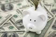 La Banca Piggy sveglia sui mucchi di contanti Fotografie Stock Libere da Diritti