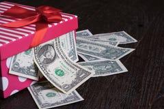 La banconota del dollaro nell'arco rosso ha decorato il contenitore di regalo Fotografie Stock Libere da Diritti