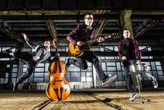 La banda rock salta nell'aria in un fabbricato industriale Fotografia Stock Libera da Diritti