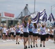 La banda y el guardia de honor adolescentes en una pequeña ciudad desfilan en América Imagenes de archivo