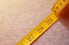 La bande de mesure de couleur jaune avec les indicateurs numériques sous forme de centimètres ou de pouces se trouve sur un tissu image stock