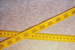 La bande de mesure de couleur jaune avec les indicateurs numériques sous forme de centimètres ou de pouces se trouve sur un tissu photo stock
