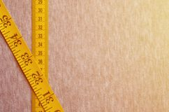 La bande de mesure jaune avec les indicateurs numériques sous forme de centimètres ou de pouces se trouve sur un tissu tricoté pa photos stock