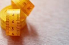 La bande de mesure jaune avec les indicateurs numériques sous forme de centimètres ou de pouces se trouve sur un tissu tricoté pa photo stock
