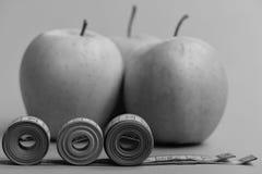 La bande de mesure proche de pommes s'enroule sur le fond vert, fin Photographie stock libre de droits