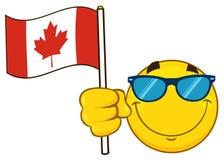 La bande dessinée jaune patriotique Emoji font face au caractère avec des lunettes de soleil ondulant un drapeau canadien Image libre de droits