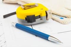 La bande jaune de mesure avec le crayon et les gants s'approchent de lui images libres de droits