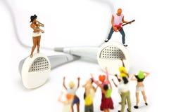 La bande miniature sur une paire d'oreille bourgeonne. Concept MP3. images stock