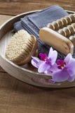 La bandeja con el cepillo y la orquídea florece para la relajación y el masaje Fotografía de archivo libre de regalías