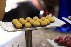 La bandeja con la bola amarilla apelmaza el canape Foto de archivo libre de regalías