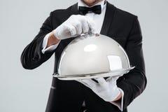 La bandeja de la porción con la campana de cristal holded por las manos de los mayordomos en guantes Foto de archivo libre de regalías
