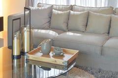 La bandeja de madera con el juego de té de la cerámica y las velas sobre el vidrio rematan la tabla Imagen de archivo