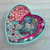 La bandeja de madera en la forma de un corazón llenó de joyería del ` s de las mujeres Imagen de archivo libre de regalías