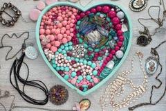 La bandeja de madera en la forma de un corazón llenó de joyería del ` s de las mujeres Imagenes de archivo