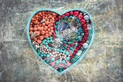 La bandeja de madera en la forma de un corazón llenó de joyería del ` s de las mujeres Fotografía de archivo