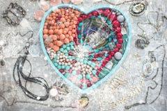 La bandeja de madera en la forma de un corazón llenó de joyería del ` s de las mujeres Imagen de archivo