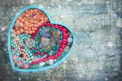 La bandeja de madera en la forma de un corazón llenó de joyería del ` s de las mujeres Fotografía de archivo libre de regalías